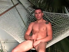 Hot guy sits down a hammock with an increment of masturbates
