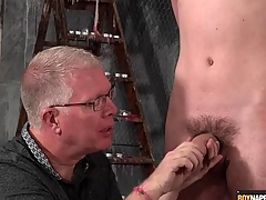 Mature BDSM master gives twink a handjob